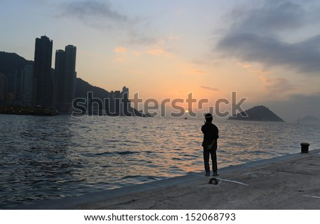 old man watching the far away under the  sunset deep thinking in the pier waiting someone back,  with the part of Hong Kong island city, beautiful background of victoria harbour  - stock photo