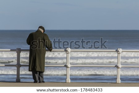 Old man with coat and hat - stock photo
