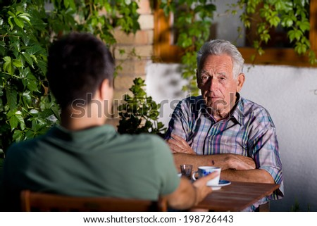 Old man with crossed hands chatting with grandson in garden - stock photo
