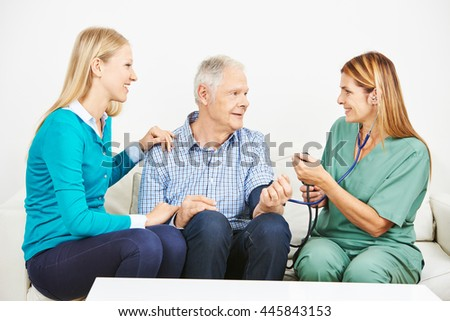Old man with granddaughter getting blood pressure monitoring - stock photo