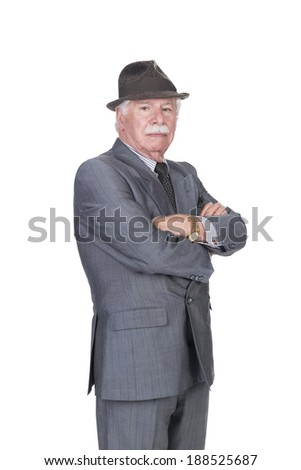 old man with gray suit and hat and folded arms in studio on a white background - stock photo