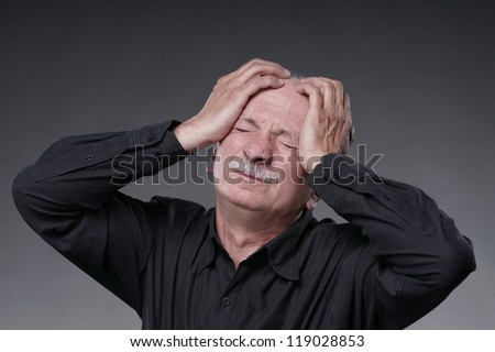 Old man with  headache on a grey background - stock photo