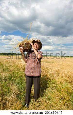Old man with knitted basket on shoulder standing in barley field - stock photo