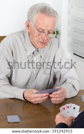 Old man with reading glasses is concentrated on playing cards - stock photo