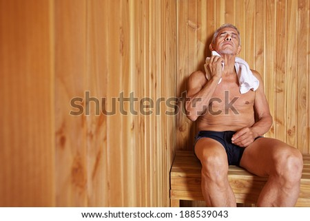 Old man with towel relaxing in sauna of a hotel - stock photo