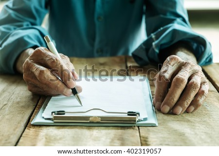 old man writing with a pencil in a notebook,Handwriting on the wood desk - stock photo