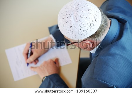Old man writing with selective focus image - stock photo