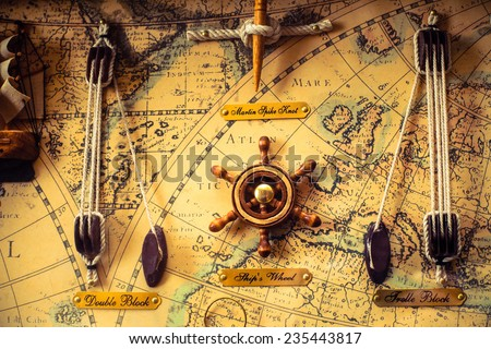 Old Map with steering wheel - stock photo