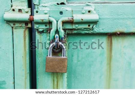 Old master key is lock on the steel door of factory. - stock photo
