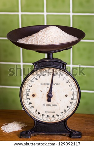 Old mechanical kitchen scales with rice in the pan - stock photo