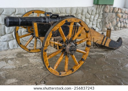 Old medieval artillery canon before a stone wall - stock photo