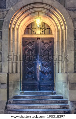 Old Medieval wooden door to church with stairs with lantern at night - stock photo