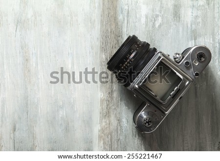 Old medium format camera and films on vintage wooden table - stock photo
