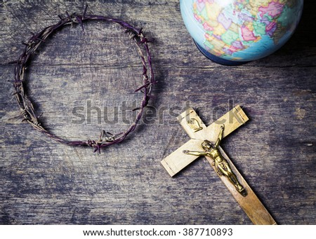 old metal Barbed Wire made like the crown of thorns of Jesus, the crucifix of Jesus and part of world globe on wooden background, Christian concept show that Jesus sacrifice himself for the world - stock photo