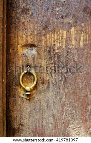 Old metal door handle knocker on a rough wooden background - stock photo