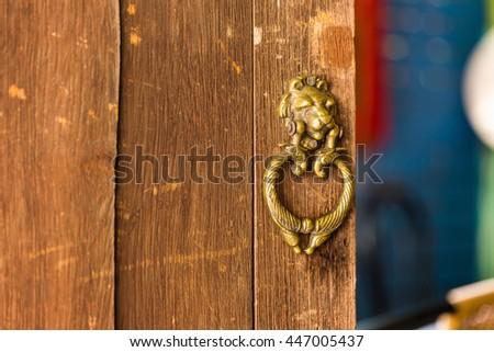 old metal door handle knocker on wood door. - stock photo