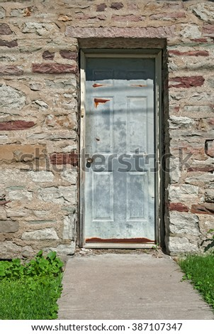 Old Metal Door in Vintage Stone House  - stock photo