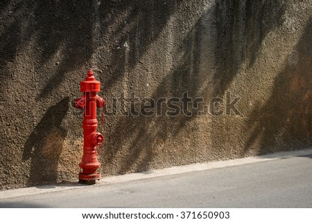 Old metal fire hydrant in front of a cement wall with shadows on street on sunny day in Croatia, Cres island - stock photo