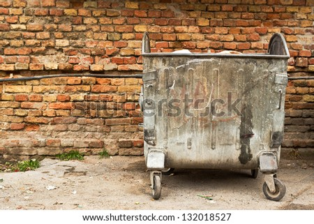 Old metal garbage containers on the street. - stock photo