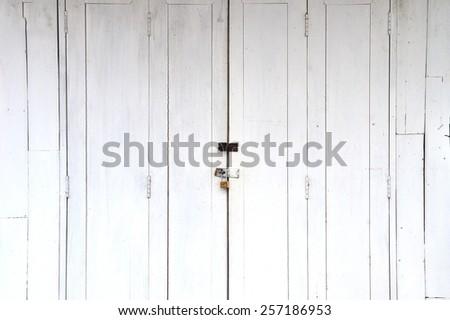 Old metal handle and padlock on white wooden door. - stock photo