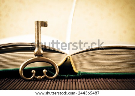 Old metal key and open book - old style photo - stock photo
