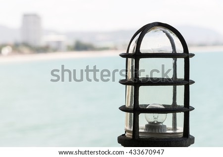 Old metal lamp of the viewpoint on the high mountain near the sea. - stock photo