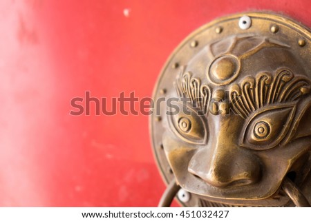 Old metal lion knocker on a red door - stock photo
