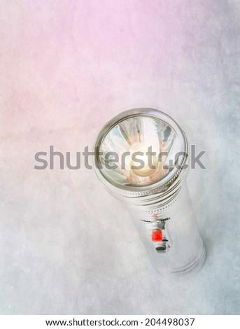 Old metal pocket flashlight over grunge background - stock photo