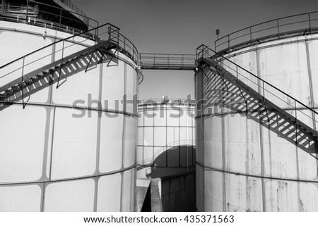 Old metal sheets l tanks in power plant, old kind of factory plant. Metal construction with old yellow paint and rusty places. Iron circle ladders around construction.  Black and white photo - stock photo