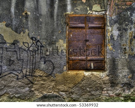 old metal window on old dirty cracked wall - stock photo