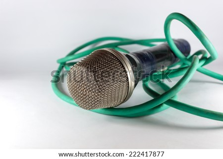 Old microphone with green cable on light background - stock photo