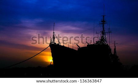 old Military war ships in sunset background - stock photo