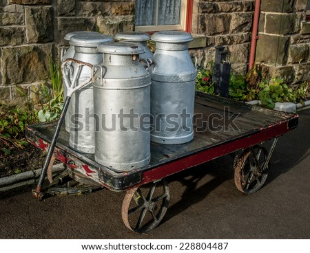 Old milk churns on a track at a railway station platform. - stock photo