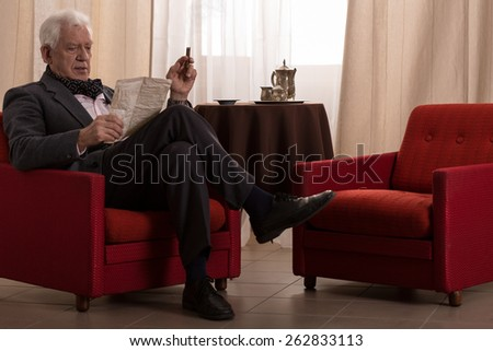Old millionaire sitting in an armchair and smoking cigar - stock photo