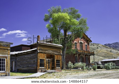 Old mining town in the mountains with large tree and blue sky - stock photo