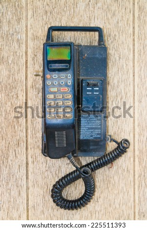 Old mobile on old desk - stock photo