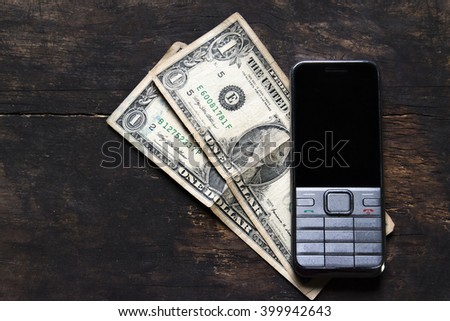 Old mobile phone and one us dollar  still life on the wood table - stock photo