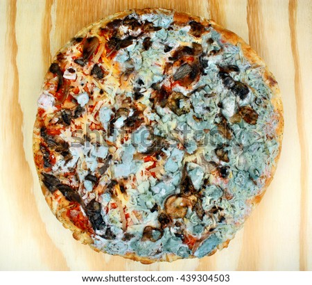 Old moldy pizza on a wooden table. Food poisoning - stock photo