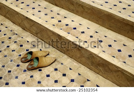 Old Moroccan (baboosh) shoes outside a mosque - stock photo