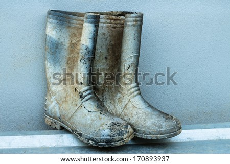 Old muddy famer boots on wall background - stock photo