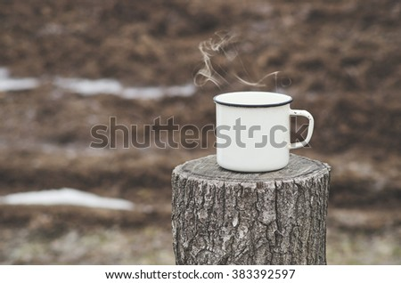 Old mug with a hot drink on a wooden stump in the outdoors. Photo in vintage color image style. Coffee break outdoors. Morning Still life. Morning at the campsite. - stock photo
