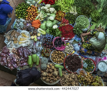 Old muslim woman selling fresh vegetables in traditional asian market - stock photo