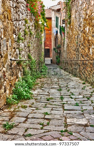 old narrow alley in tuscan village - antique italian lane in Montalcino, Tuscany, Italy - stock photo