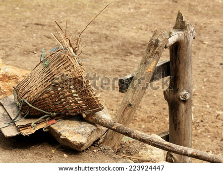 Old Nepalese basket rests on a stone. Nepal. - stock photo