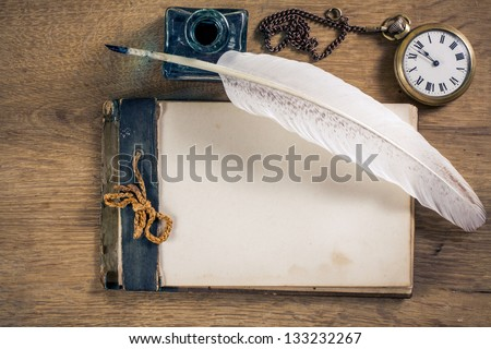 Old notebook, quill and pocket watch on wood - stock photo