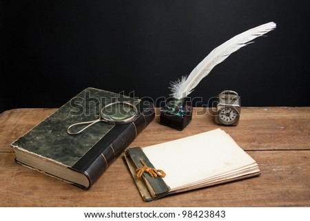 Old notepad, antique book, quill ink pen and inkwell, magnifying glass, vintage clock on wood table - stock photo