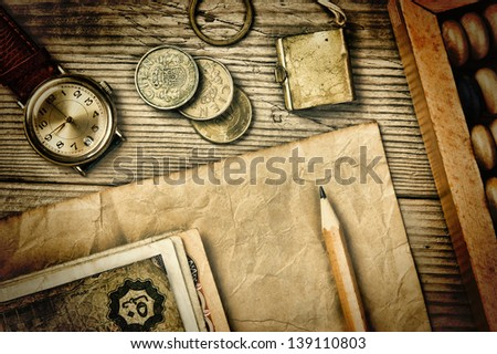 Old notes and coins and abacus on a wooden table - stock photo