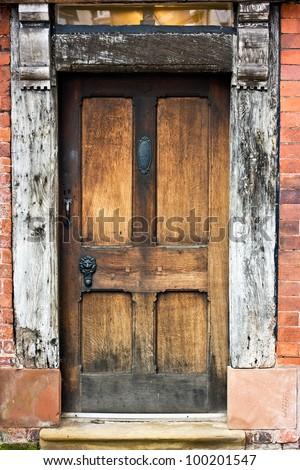 Old Oak door, frame, and window of tudor building. - stock photo
