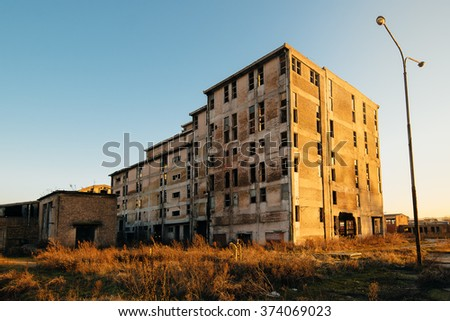 Old obsolete industrial building ruined and ready for demolishing, wide angle shot of abandoned factory construction. - stock photo