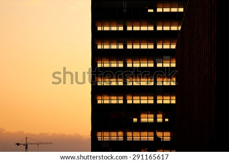 Old office building being deconstructed filled with sunset light. Sunset light going through skeleton of dismantled office building. - stock photo